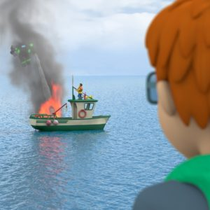 """FIREMAN SAM™ NORMAN PRICE & THE MYSTERY IN THE SKY MOVIE STILL :  The professor races to the rescue in the suit. Norman — dressed as Norman-Man — looks on in awe. """"Wooow, if I had a suit like that I'd be the best hero ever,"""" he says."""